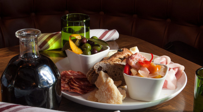 Dionysos' Delight, a special antipasti platter with tomato mostarda, prosciutto de parma, giardiniera, some other kind of meat and two kinds of cheese, served with a carafe of sangiovese red wine.
